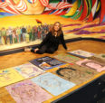 Esperanza Gama sitting by the 10 pieces of collaborative art