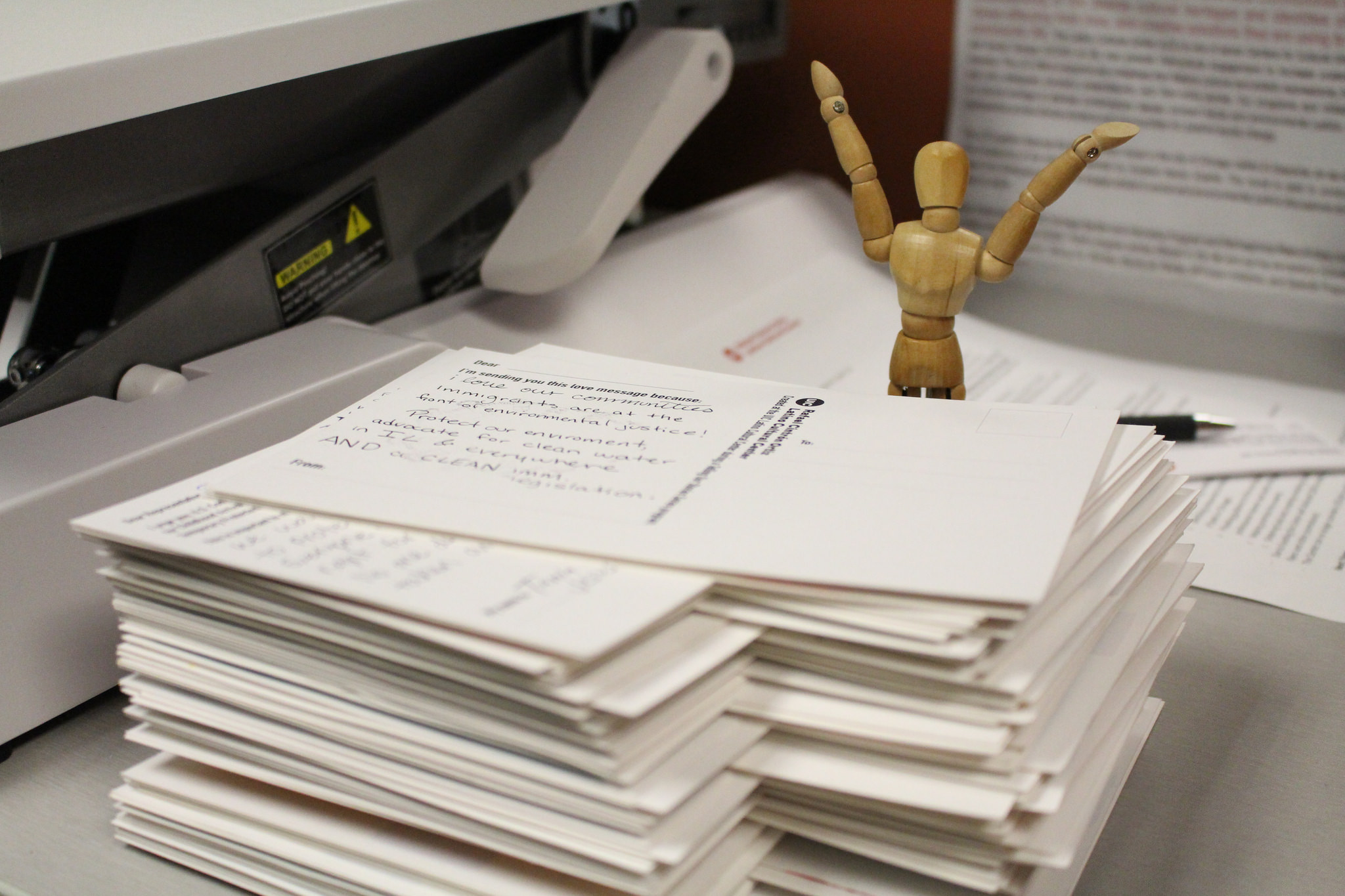 image of a Stack of Post Cards with happy figurine behind it