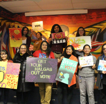 artists, students, and staff holding voting posters