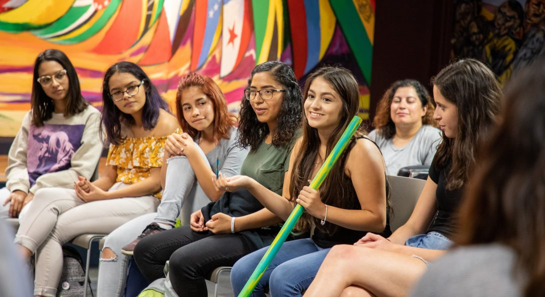 Students from L@s Ganas during a storytelling event. Woman is holding the talking stick while classmates listen.